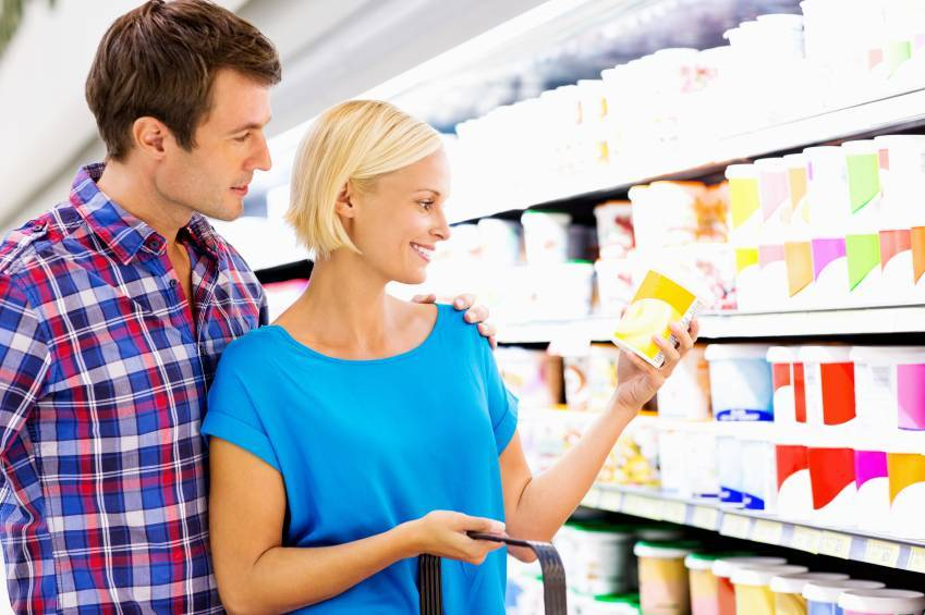 Woman Checking Product Nutrition Label With Man In Supermarket