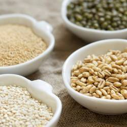Raw Organic Amaranth and quinoa grains, wheat and mung beans in small bowls
