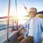 successful retired man sailing portrait at sunrise on boat