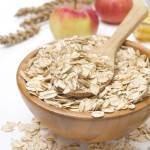 Oat flakes in a wooden bowl and apples in the background, isolated on white, close-up